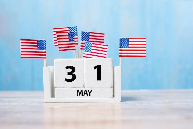 31 de maio do calendário branco com a bandeira dos estados unidos da américa em fundo de madeira. dia do memorial 2021 e conceito de férias