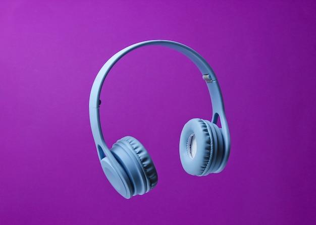 3d cercam fones de ouvido sem fio azuis da foto em um fundo roxo.