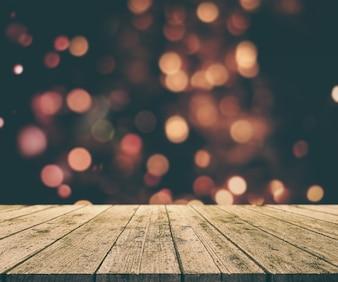 3D rendem de um fundo de Natal com tabela de madeira velha de encontro às luzes do bokeh de fundo