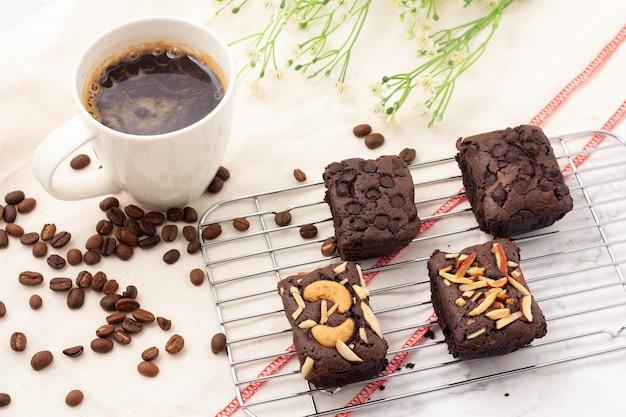 4 brownies escuros quadrados com gotas de chocolate, amêndoas e nozes em uma assadeira, 1 xícara de café branco e grãos de café colocados em um pano branco.