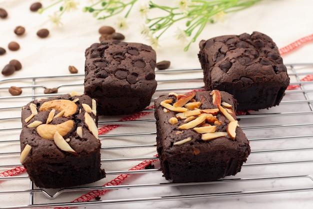 4 brownies escuros quadrados com gotas de chocolate, amêndoas e nozes em uma assadeira, grãos de café colocados em um pano branco.