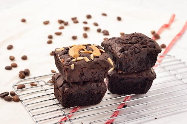 4 brownies escuros quadrados com gotas de chocolate, amêndoas e nozes em uma assadeira, grãos de café colocados sobre um pano branco, vista lateral.