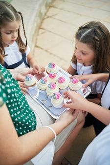 4 colegas pegando cupcakes de uma bandeja segurada pela professora