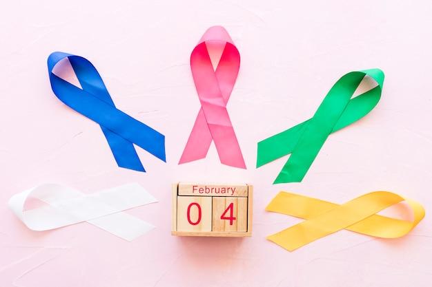 4 de fevereiro caixa de madeira em torno das fitas coloridas no fundo rosa
