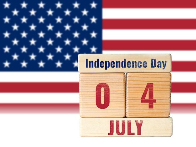 4 de julho dia da independência, calendário de blocos de madeira com bandeira dos estados unidos desfocado