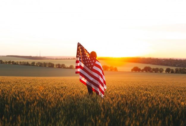 4 de julho. mulher com a bandeira americana correndo em um campo de trigo ao pôr do sol. dia da independência, feriado patriótico.