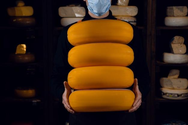 4 grandes rodas amarelas de queijos nas mãos. vendedor com máscara para proteção contra o coronavírus covid-19. segurando o queijo redondo.