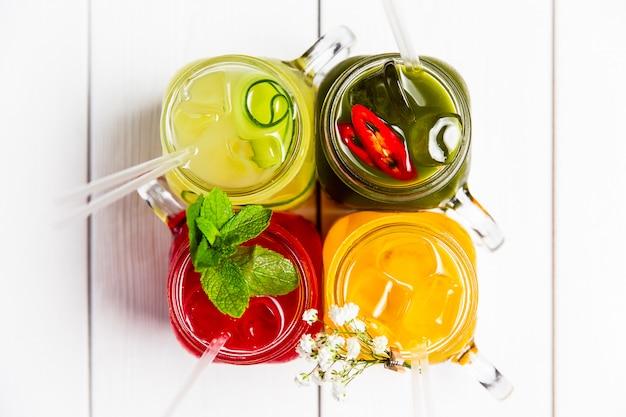 4 limonadas de verão refrescantes diferentes em frascos, vermelho, laranja, amarelo e verde, vista superior