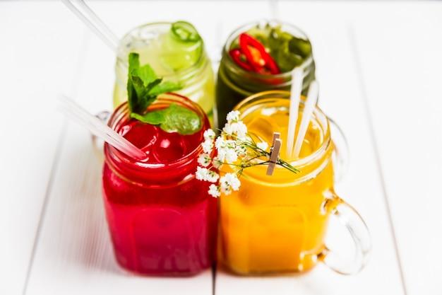 4 limonadas de verão refrescantes diferentes em frascos, vermelho, laranja, amarelo e verde