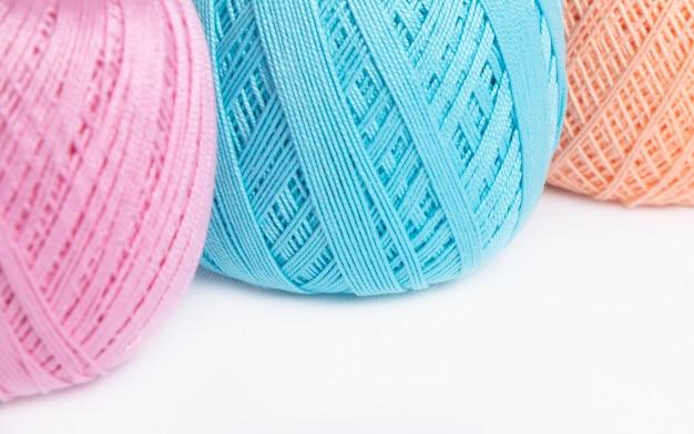 4 novelos de linha de lã em um fundo branco rosa, azul, verde e pêssegos