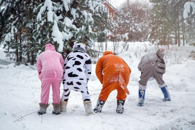 4 pessoas em kigurumi na neve inverno floresta pijama porco vaca gato canguru diversão com amigos caminhando