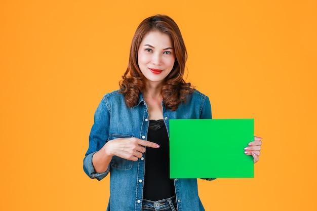 45s fofo cabelo encaracolado bonito mulher asiática segurando papelão verde em branco, studio um tiro com flash de luz em fundo amarelo brilhante. adicionada ideia para conteúdo publicitário.