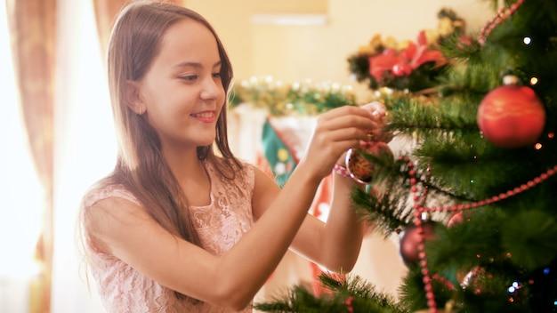 4k filmagens de uma bela adolescente sorridente pendurando bugigangas coloridas na árvore de natal em casa. casa de decoração familiar nas festas e feriados de inverno.