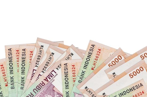 5.000 notas de rupias indonésias na parte inferior da tela, isoladas no fundo branco com espaço de cópia