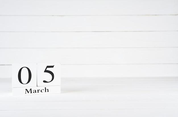 5 de março, dia 5 do mês, aniversário, aniversário, calendário de bloco de madeira sobre fundo branco de madeira com espaço de cópia para o texto.