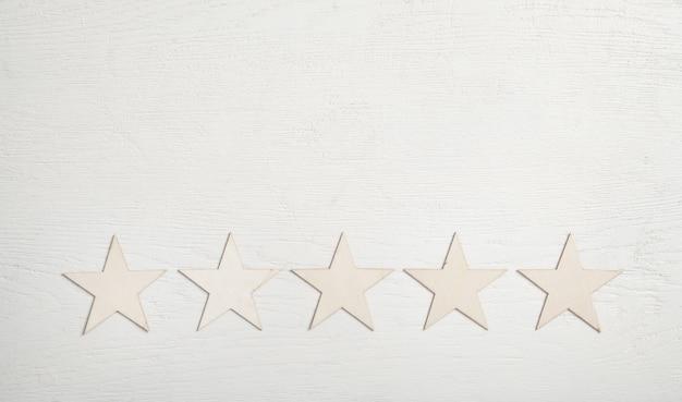 5 estrelas de madeira em fundo branco. avaliação de serviço