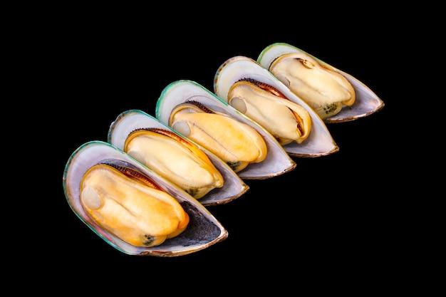 5 mexilhões da nova zelândia frescos descascados, dispostos isolados em um fundo preto. frutos do mar populares. grandes mexilhões da nova zelândia preparados para cozinhar.