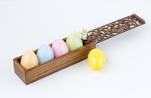 5 ovos pintados em uma caixa de madeira