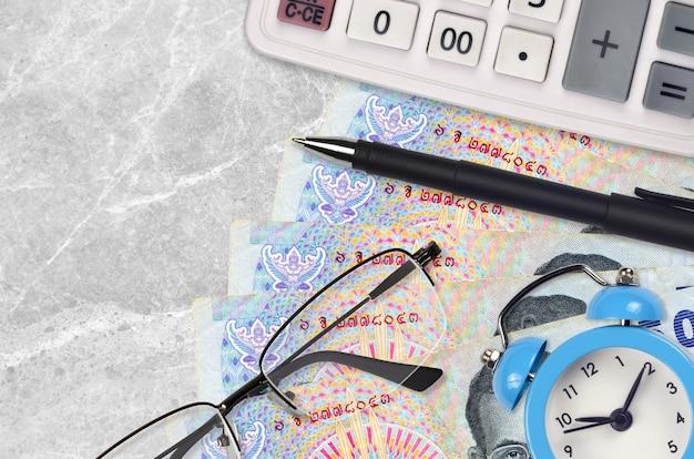 50 contas de baht tailandês e calculadora com óculos e caneta