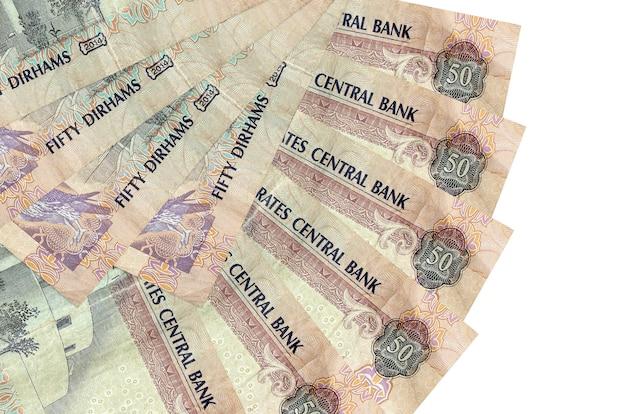 50 contas de dirhams dos emirados árabes unidos encontram-se isoladas na parede branca com espaço de cópia empilhados em forma de leque close-up. conceito de transações financeiras
