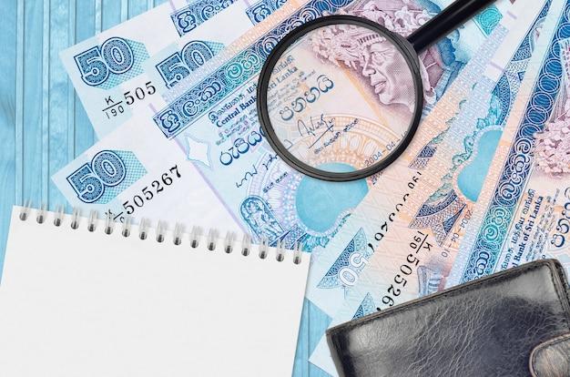 50 notas de rúpias do sri lanka e lupa com bolsa preta e bloco de notas