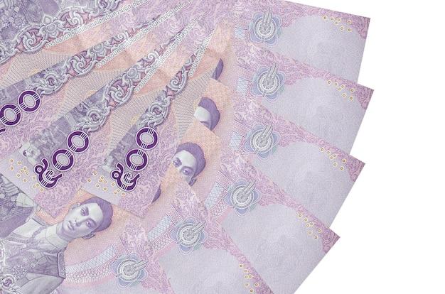 500 contas de baht tailandês encontram-se isoladas na parede branca com espaço de cópia empilhados em forma de leque close-up. conceito de transações financeiras