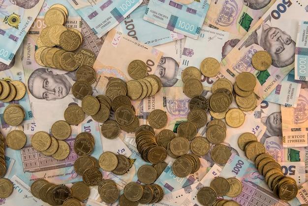 500 e 1000 notas de dinheiro ucraniano como moeda de ouro de fundo deitada na pilha de dinheiro de grivna caoncept