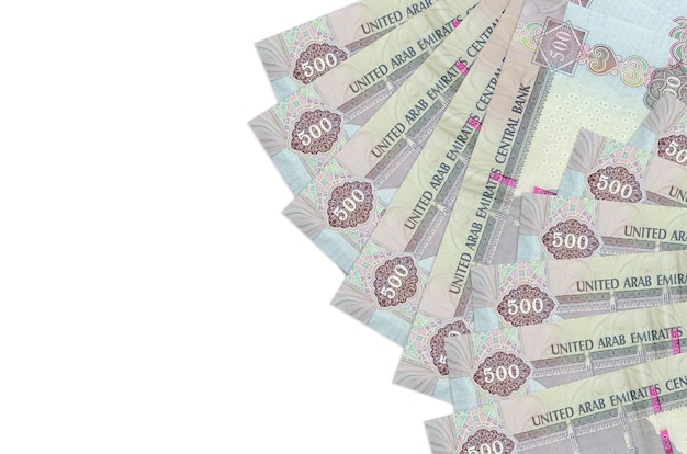 500 notas de dirhams dos emirados árabes unidos encontram-se isoladas na parede branca, com espaço de cópia. parede conceitual de vida rica. grande quantidade de riqueza em moeda nacional