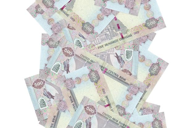 500 notas de dirhams dos emirados árabes unidos voando baixo isoladas no branco. muitas notas caindo com espaço de cópia em branco no lado esquerdo e direito