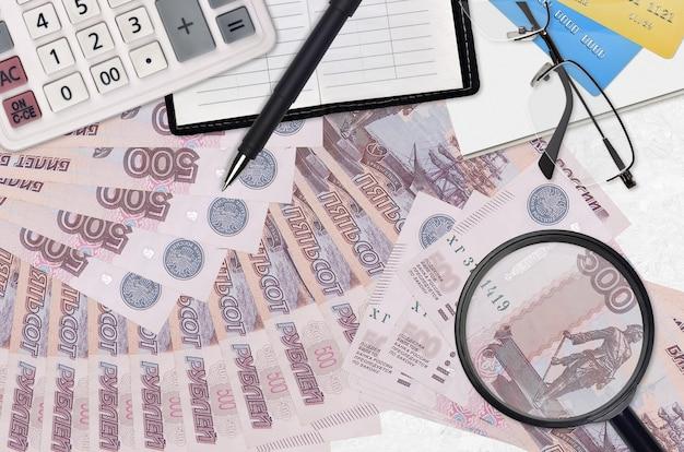 500 notas de rublos russos e calculadora com óculos e caneta