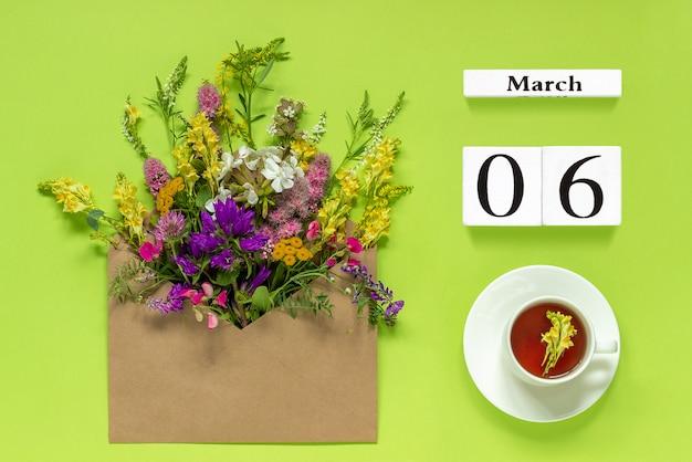 6 de março. xícara de chá de ervas, envelope kraft com multi flores coloridas