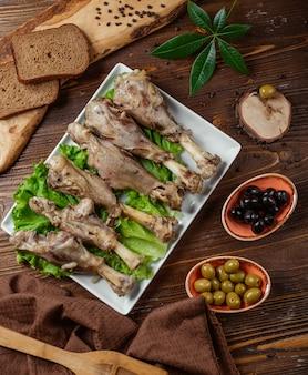 6 pedaços de pernas de peru cozidas servidas com azeitonas pretas e verdes, pão