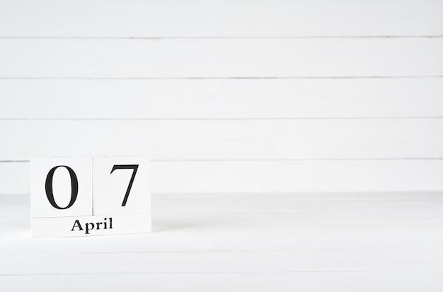 7 de abril, dia 7 do mês, aniversário, aniversário, calendário de bloco de madeira no fundo de madeira branco com espaço da cópia para o texto.
