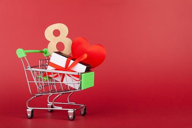 8, caixas de presente de coração, preto e branco com fita vermelha em carrinho de mão de compras em fundo vermelho, conceito de vendas e amor, dia da mulher, dia dos namorados, espaço de cópia, horizontal
