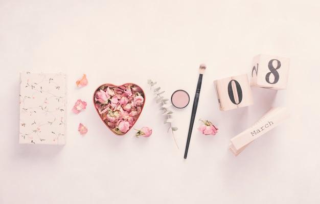 8 de março de inscrição com pétalas de rosa e pincel na mesa