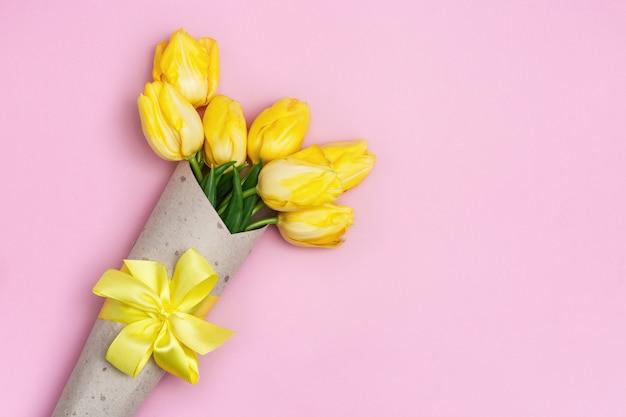 8 de março o conceito do dia das mulheres da mãe com tulipas amarelas floresce no saco de papel.