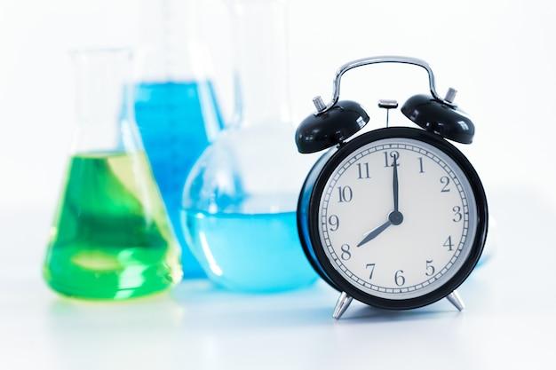 8 horas relógio retrô com fundo de laboratório de pesquisa médica da ciência química