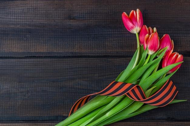 9 de maio fundo - tulipas vermelhas, fita de george no fundo de madeira. dia da vitória ou conceito do dia do defensor da pátria. vista superior, copie o espaço para texto
