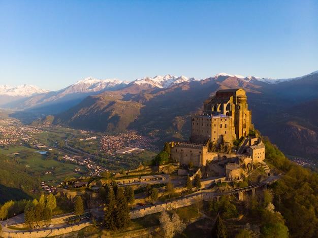 A abadia medieval velha da vista aérea empoleirou-se na parte superior da montanha, cumes nevado do fundo no nascer do sol. sacra di san michele turim, itália