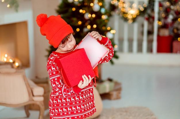A abertura da criança está presente na árvore de natal em casa menino de pijama vermelho com presentes