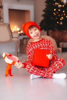 A abertura da criança está presente na árvore de natal em casa. rapaz de pijama vermelho com presentes de natal. menino com uma caixa de presente e doces para a árvore de natal. decoração para casa.