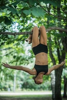A acrobata da menina executa o elemento acrobático na árvore. mulher, acoplado, em, ginástica