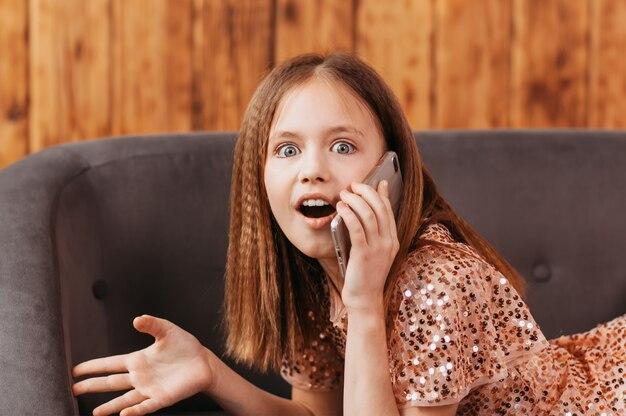 A adolescente está falando ao telefone e fica surpresa. emoções e expressão