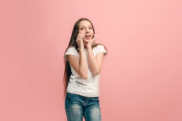 A adolescente feliz em pé e sorrindo contra a parede rosa