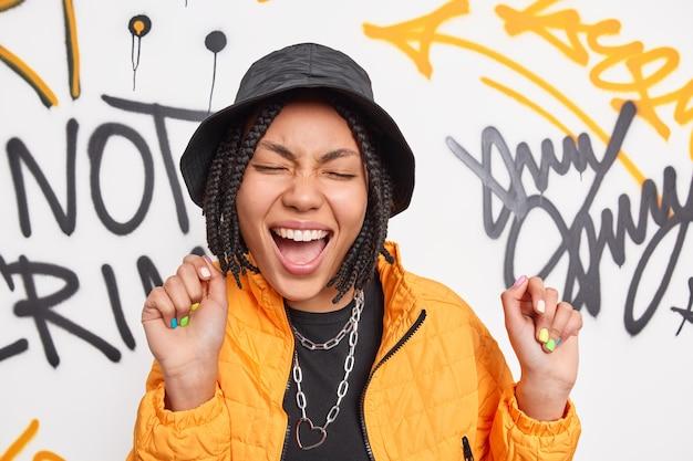 A adolescente feminina urbana elegante dança despreocupada com uma expressão feliz contra a parede de graffiti, usa roupas da moda, sendo uma artista de rua, tem uma aparência legal, aproveita o tempo livre e expressa emoções positivas