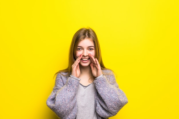 A adolescente grita, tendo combinado as mãos em um megafone isolado