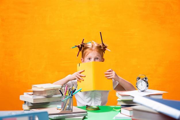 A adolescente ruiva com muitos livros em casa. foto de estúdio