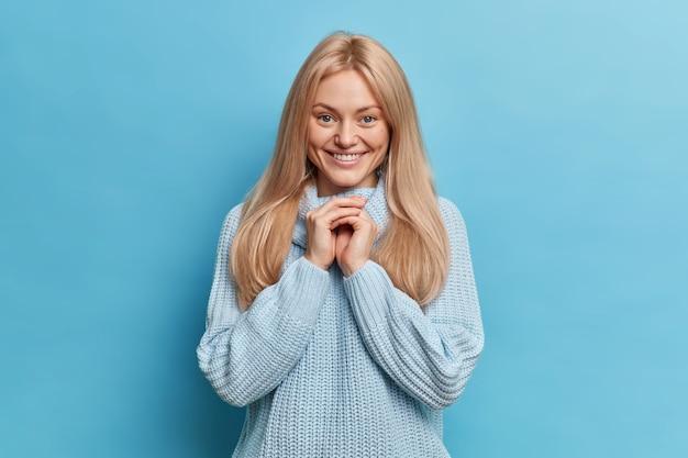 A adorável loira européia sorri suavemente, mantém as mãos juntas enquanto covinhas nas bochechas usa um suéter de tricô ouve algo agradável