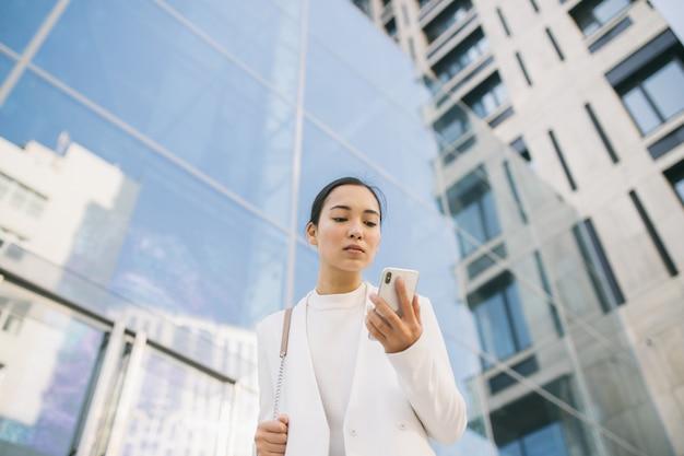 A advogada bonita asiática adulta está andando na frente do centro do escritório, olhando em seu celular lendo a massagem do cliente