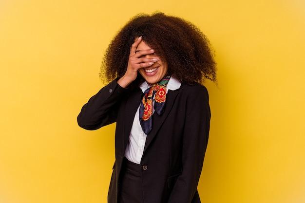 A aeromoça afro-americana jovem isolada em um fundo amarelo pisca para a câmera por entre os dedos, o rosto coberto de vergonha.